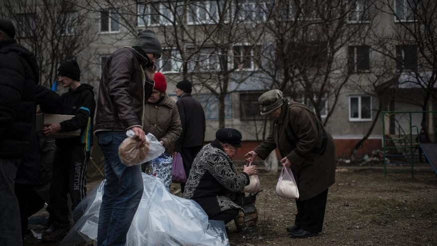 Local residents receive humanitarian aid after Saturday's shelling at Vostochniy district of Mariupol, Ukraine, Monday, Jan. 26, 2015. At least 5,100 people have been killed in eastern Ukraine since fighting began in April, but violence this week was the most intense since a cease-fire deal was signed in September. (AP Photo/Evgeniy Maloletka)