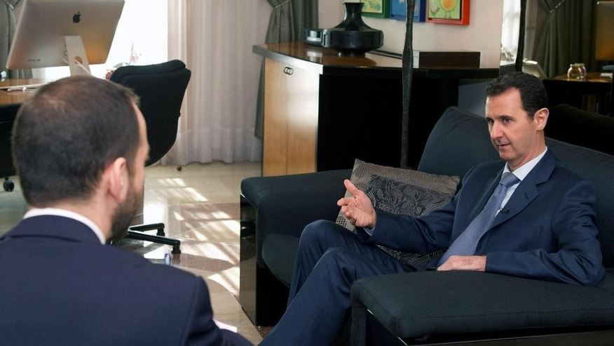 "In this photo released by the Syrian official news agency SANA, Syrian President Bashar Assad, right, speaks during an interview with a U.S. magazine, in Damascus, Syria, Monday, Jan. 26, 2015. Assad has dismissed negotiations with ""puppets"" in an interview with a U.S. magazine ahead of talks set to begin in Moscow. (AP Photo/SANA)"