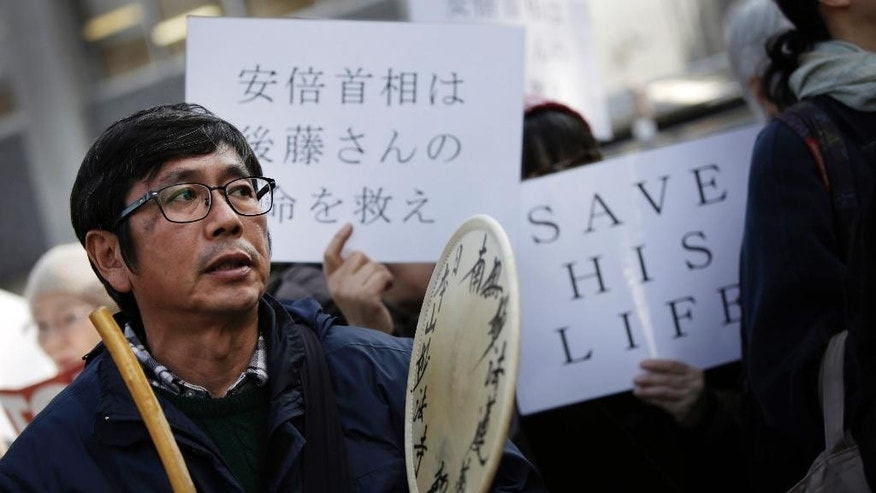 "A man beats a drum as he and others demand the release of Japanese journalist Kenji Goto, taken hostage by Islamic State, during a rally outside the prime minister's official residence in Tokyo, Tuesday, Jan. 27, 2015. A Japanese envoy in Jordan expressed hope that both a Japanese hostage and a Jordanian pilot held by Islamic militants will return home ""with a smile on their faces,"" as criticisms mounted Tuesday over the government's handling of the crisis. The placard at left reads: ""Prime Minister Abe should save Mr.Goto's life."" (AP Photo/Eugene Hoshiko)"