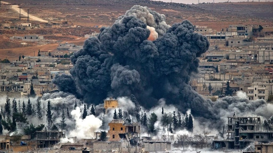Smoke rises from the Syrian city of Kobani, following an airstrike by the U.S.-led coalition in November. (AP Photo/Vadim Ghirda, File)