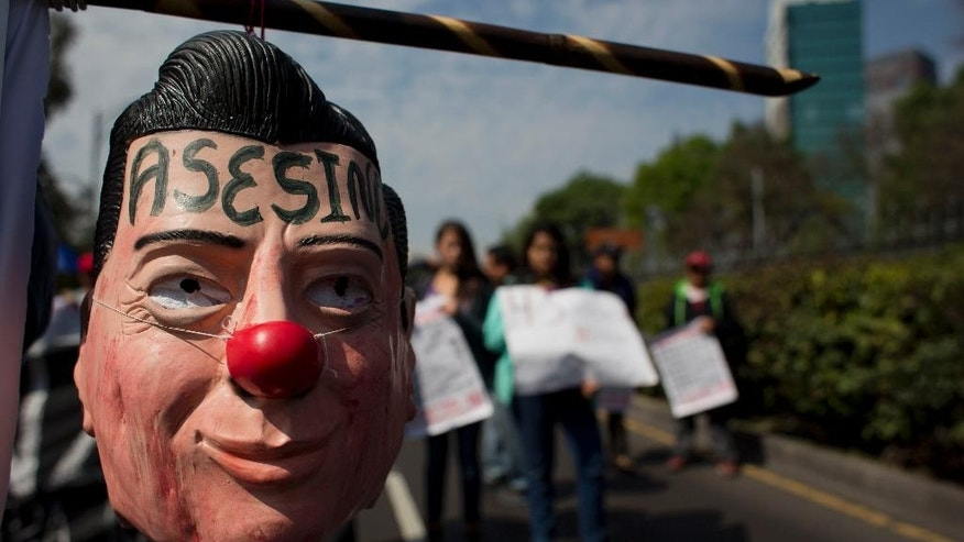 """A protestor carries a hanging mask of Mexican President Enrique Pena Nieto marked with the word in Spanish """"Assassin"""" during a march in Mexico City, Monday, Jan. 26, 2015. Protest marches were planned in cities around the country to mark the fourth month since the disappearance of 43 students in southern Guerrero state. The federal prosecutor has said the students were detained by local police and handed over to a drug gang, who killed them and burned their bodies. (AP Photo/Rebecca Blackwell)"""