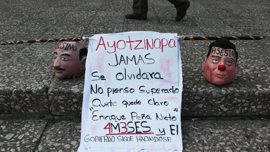 """Masks in the likeness of Mexico's President Enrique Pena Nieto, right, and former President Carlos Salinas, covered with the Spanish word """"Assassin,"""" sit next to a sign during a protest against the disappearance of 43 students from a rural teachers college in Guerrero state on the fourth month since they went missing, in Mexico City, Monday, Jan. 26, 2015. The sign reads in Spanish """"Ayotzinapa will never be forgotten. I don't plan on getting over it. May it be clear """"Enrique Pena Nieto,"""" four months."""" The federal prosecutor has said the students were detained by local police and handed over to a drug gang, who killed them and burned their bodies. (AP Photo/Marco Ugarte)"""