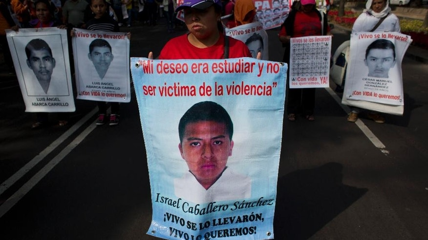 """Protestors carry banners with pictures of some of the 43 missing students from a rural teachers college, as they march along a main boulevard in Mexico City, Monday, Jan. 26, 2015. The banner of Israel Caballero Sanchez reads """"My desire was to study and not to be a victim of violence,"""" and """"They took them alive. We want them back alive."""" Protest marches were planned in cities around the country to mark the fourth month since the disappearance of the students in southern Guerrero state. The federal prosecutor has said the students were detained by local police and handed over to a drug gang, who killed them and burned their bodies.(AP Photo/Rebecca Blackwell)"""