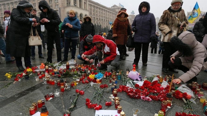 People light candles and lay flowers on Independence Square in Kiev, Ukraine, Sunday, Jan. 25, 2015, for the victims of a rocket attack on the coastal city of Mariupol. Indiscriminate rocket fire slammed into a market, schools, homes and shops Saturday in Ukraine's southeastern city of Mariupol, killing at least 30 people, authorities said. The Ukrainian president called the blitz a terrorist attack and NATO and the U.S. demanded that Russia stops supporting the rebels. (AP Photo/Sergei Chuzavkov)