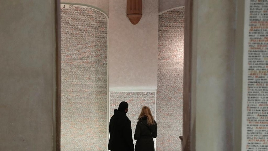 In this picture taken in Prague, Czech Republic, Wednesday, Jan. 21, 2015, tourists read names of holocaust victims written on the walls of Pinkas synagogue. On Tuesday, Jan. 27, 2015 we celebrate 70th anniversary of liberation of concentration camp Auschwitz. (AP Photo/Petr David Josek)