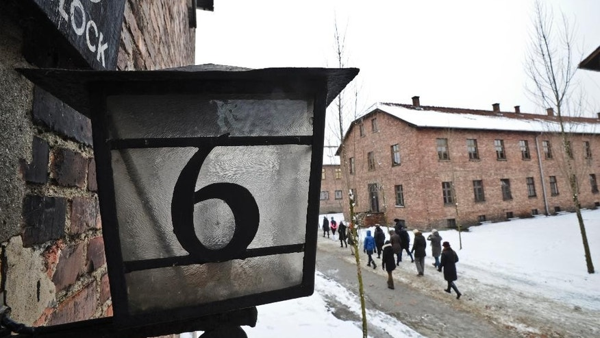 Visitors pass by the detention building marked Block 6 at the Auschwitz Nazi death camp in Oswiecim, Poland, Monday, Jan. 26, 2015. A decade ago, 1,500 Holocaust survivors traveled to Auschwitz to mark the 60th anniversary of the death camp's liberation. On Tuesday, for the 70th anniversary, organizers are expecting 300, the youngest in their 70s. (AP Photo/Alik Keplicz)