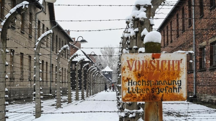 Visitors walk between barbed wire fences at the Auschwitz Nazi death camp in Oswiecim, Poland, Monday, Jan. 26, 2015. A decade ago, 1,500 Holocaust survivors traveled to Auschwitz to mark the 60th anniversary of the death camp's liberation. On Tuesday, for the 70th anniversary, organizers are expecting 300, the youngest in their 70s. Sign in foreground is an electric fence warning.(AP Photo/Alik Keplicz)