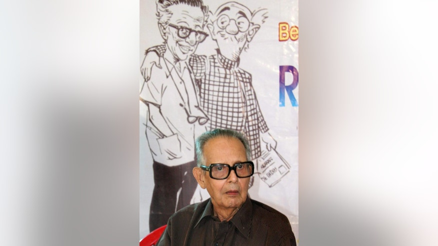 This undated photograph shows acclaimed Indian cartoonist R. K. Laxman seated in front of a poster of the 'Common Man', wearing checked shirt, in India. Laxman, who created the innocuous character the 'Common Man' who held up a mirror to the absurdity and silliness of Indian politicians, died of multiple-organ failure Monday, Jan. 26, 2015, his doctor said. Laxman's almost daily Common Man cartoon was a commentary on Indian society and politics that ran in the Times of India newspaper for more than five decades. (AP Photo/Press Trust of India)