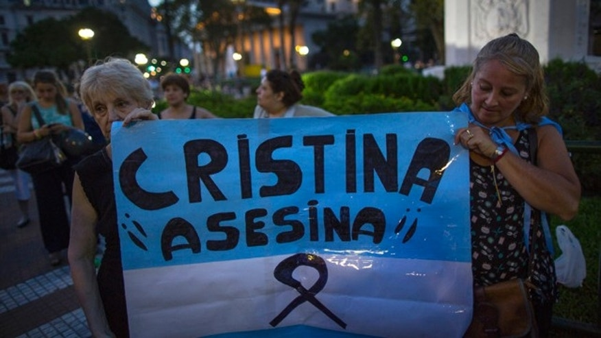 Jan. 26, 2015: Protesters hold a replica of the Argentine flag that reads in Spanish 'Cristina Assassin,' referring to President Cristina Fernandez as she delivers a live televised speech, her first public comments since the mysterious death of a prosecutor in Buenos Aires. (AP Photo/Ivan Fernandez)