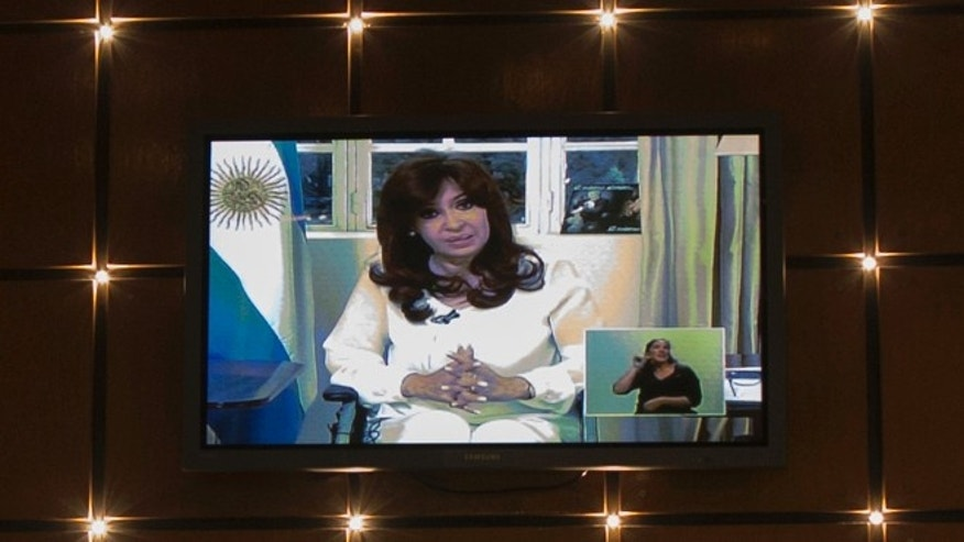 A television screen in a restaurant shows a nationally televised address by Argentina's President Cristina Fernandez, her first public comments since the death of prosecutor Alberto Nisman, in Buenos Aires, Argentina, Monday, Jan. 26, 2015. Fernandez called on Congress to dissolve Argentina's intelligence services in the wake of the mysterious death of Nisman, strongly denying his accusations that she had sought to shield former Iranian officials suspected in the 1994 bombing of a Jewish center. (AP Photo/Ivan Fernandez)