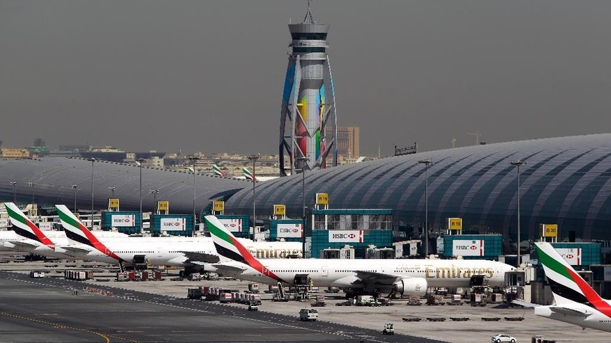 FILE- In this May 8, 2014 file photo, Emirates passenger planes are parked at their gates of Dubai airport in United Arab Emirates. Dubai's airport operator released figures Tuesday showing that 70.5 million passengers streamed through the sparkling halls of the Gulf commercial hub's main airport last year. The rapid growth puts Dubai squarely ahead of London Heathrow for the first time as the world's busiest international air hub. (AP Photo/Kamran Jebreili, File)