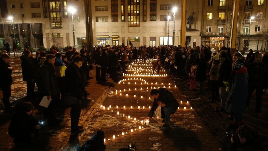 People light candles on Independence Square in Vilnius, Lithuania, Monday, Jan. 26, 2015, in solidarity with the victims of a rocket attack on the coastal city of Mariupol. Indiscriminate rocket fire slammed into a market, schools, homes and shops Saturday in Ukraine's southeastern city of Mariupol, killing at least 30 people, authorities said. (AP Photo/Mindaugas Kulbis)