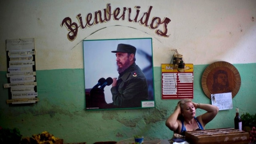 Dec. 26, 2014: A photograph of Fidel Castro hangs under the Spanish word 'Welcome' on the wall at a state-run food market in Havana, Cuba. (AP Photo/Ramon Espinosa, File)