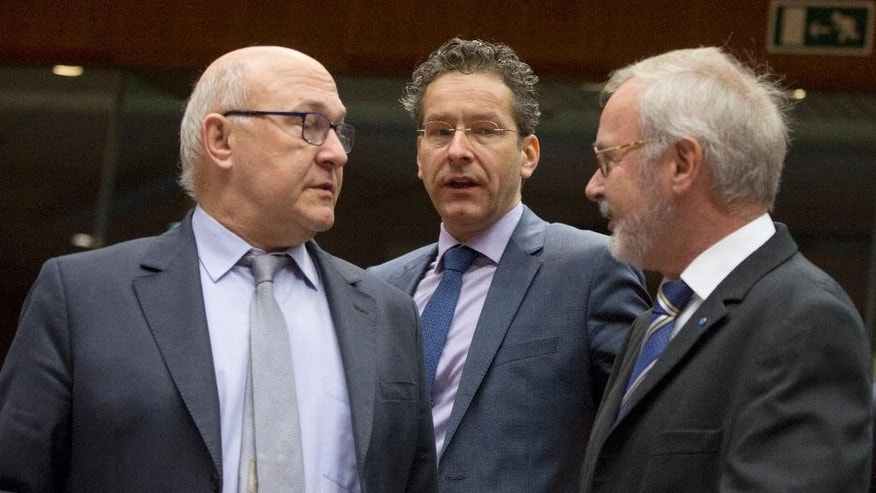 Dutch Finance Minister Jeroen Dijsselbloem, center, walks by French Finance Minister Michel Sapin, left, and European Investment Bank President Werner Hoyer, right, during a meeting of EU finance ministers at the EU Council building in Brussels on Tuesday, Jan. 27, 2015. France is urging its EU partners to step up the fight against terror financing and will propose new measures to make sure transactions are more transparent. (AP Photo/Virginia Mayo)
