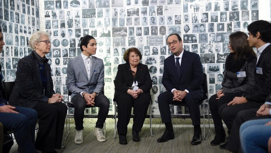 French President Francois Hollande, center right,  speaks with five Jews deported and five young Jews, Tuesday Jan. 27, 2015 in Paris, at the Holocaust memorial.  Hollande visits France's Holocaust Memorial, amid rising concerns about anti-Semitism after a kosher supermarket was targeted in the country's deadliest attacks in decades. Hollande heads later in the day to Auschwitz for the 70th anniversary of the liberation of the Nazi concentration camp. (AP Photo/Martin Bureau, Pool)