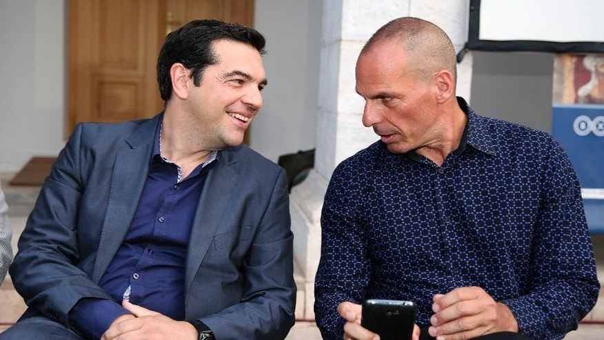 In this Monday, June 16, 2014 photo Greece's new Prime Minister Alexis Tsipras, left, attends a book presentation of Yanis Varoufakis, right, in Athens. Economist and outspoken bailout critic Yanis Varoufakis, 53, has confirmed on Tuesday, Jan. 27, 2015 in a blog post that he will be sworn in as Finance Minister under the country's new left wing government. (AP Photo/InTime News, Giannis Liakos)  GREECE OUT