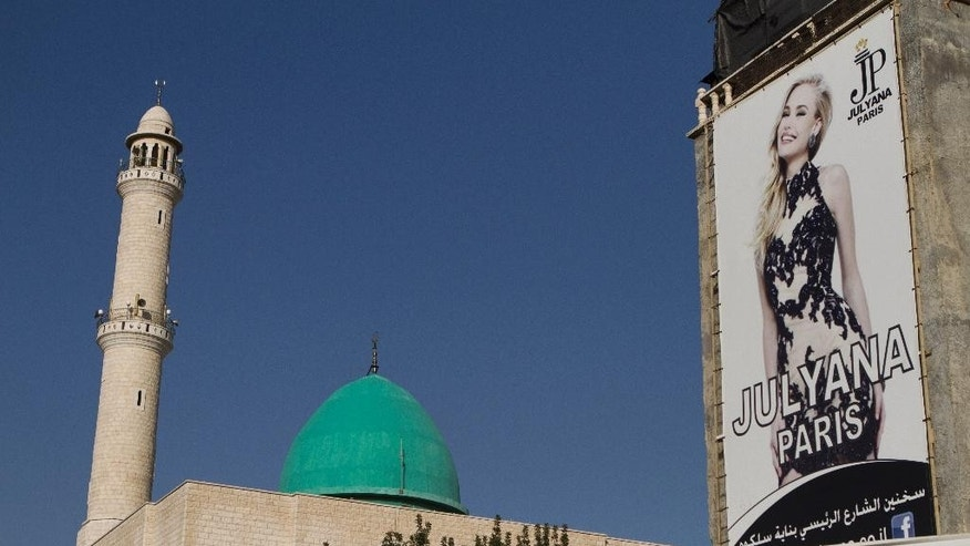 An advertisement for European fashion is displayed next to a Mosque in the Arab city of Sakhnin, about 23 kilometers (14 mi) east of Acre, Israel, Monday, Jan. 26, 2015. Coping with new election laws that make it harder for smaller parties to enter Israel's parliament, the country's Arab political parties for the first time are banding together under one ticket to boost their chances in upcoming national elections. Arab politicians say it will improve chronically low Arab voter turnout and help block Netanyahu from forming the next government. (AP Photo/Dan Balilty)