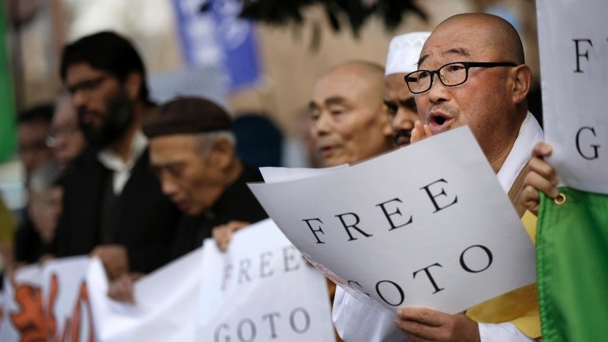 "Buddhist monks and other religious group members hold banners and placards to voice their demand about the release of Japanese journalist Kenji Goto taken by the Islamic State, during a rally outside the Prime Minister's official residence in Tokyo, Tuesday, Jan. 27, 2015. A Japanese envoy in Jordan expressed hope that both a Japanese hostage and a Jordanian pilot held by Islamic militants will return home ""with a smile on their faces,"" as criticisms mounted Tuesday over the government's handling of the crisis. (AP Photo/Eugene Hoshiko)"