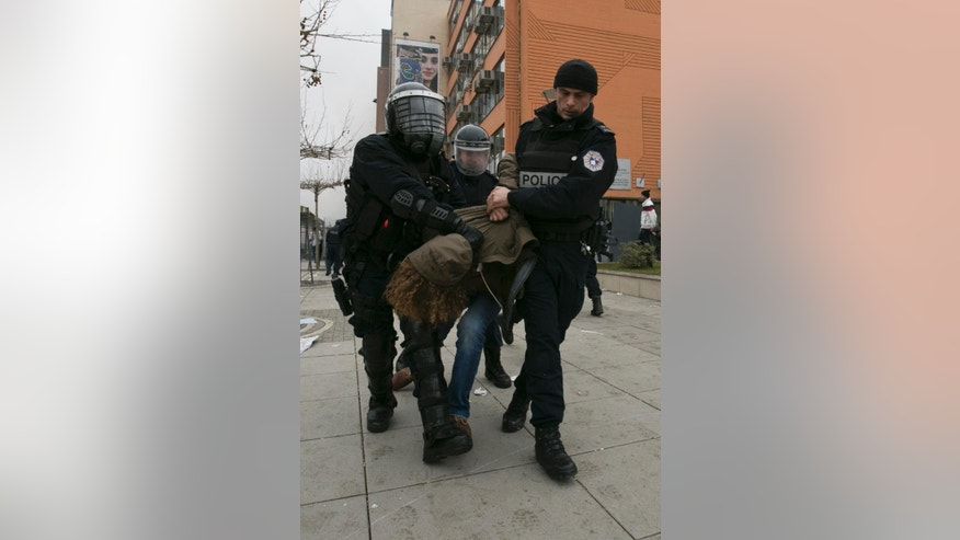 Police officers detain a protester during a demonstration in Kosovo's capital Pristina, Tuesday, Jan. 27, 2015. Police in Kosovo fired volleys of tear gas at thousands of anti-government protesters demanding the resignation of a minister who had denied that war crimes were committed against ethnic Albanians during the 1998-99 war with Serbia. (AP Photo/Visar Kryeziu)