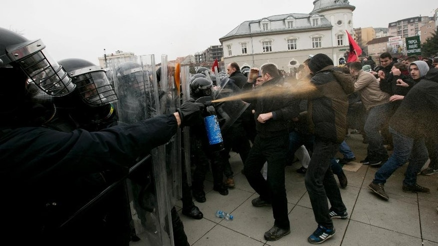 Police in riot gear spray pepper spray during a protest in Kosovo's capital Pristina, Tuesday, Jan. 27, 2015. Police in Kosovo fired volleys of tear gas at thousands of anti-government protesters demanding the resignation of a minister who had denied that war crimes were committed against ethnic Albanians during the 1998-99 war with Serbia. (AP Photo/Visar Kryeziu)