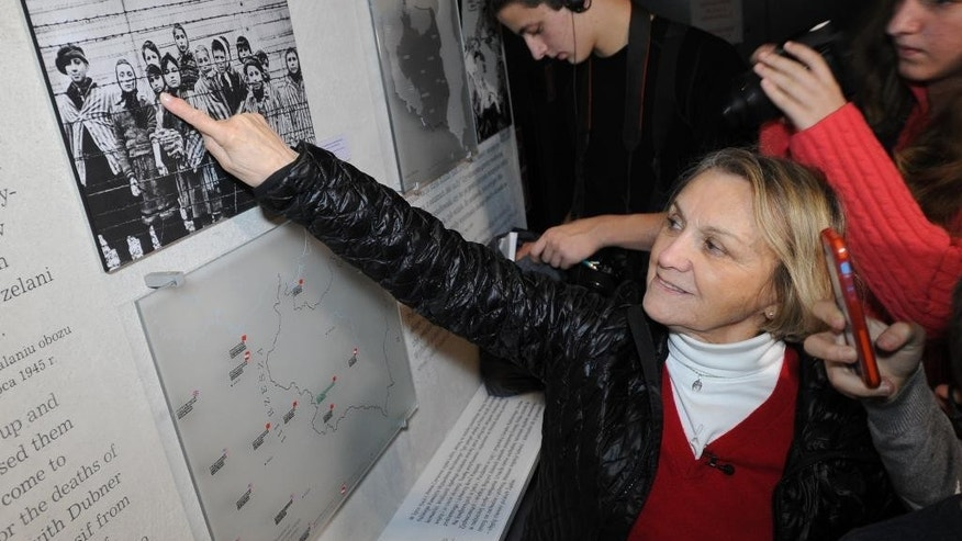 In this Saturday, Jan. 24, 2015 photo Paula Lebovics, an 81-year-old Holocaust survivor points to a photo showing herself as a child and other children at the Auschwitz-Birkenau Nazi death camp pictured after the camp was liberated by the Soviet Red Army, at the POLIN Museum of the History of Polish Jews, in Warsaw, Poland. Lebovics was 11 at that time. (AP Photo/Alik Keplicz)