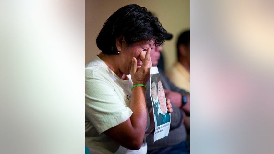 A relative holding a picture of one of the missing students, wipes a tear from her face during a press conference by the family members of the missing, in Mexico, City, Tuesday Jan. 27, 2015. Mexican attorney general Jesus Murillo Karam said that investigators are now certain that 43 college students missing since September were killed and incinerated after they were seized by police in southern Guerrero state. It was the first time Murillo Karam said definitely that all were dead, even though Mexican authorities have DNA identification for only one student and a declaration from a laboratory in Innsbruck, Austria, that it appears impossible to identify the others. (AP Photo/Eduardo Verdugo)