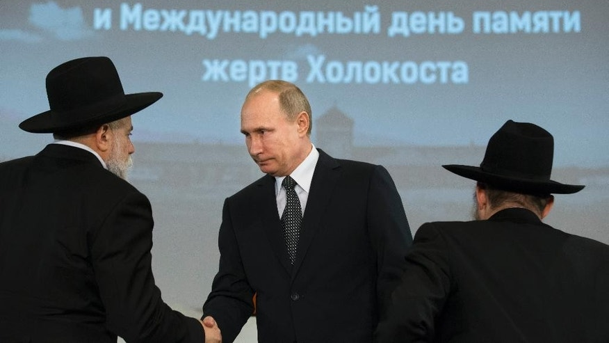 Russian President Vladimir Putin, center, shakes hands with Chairman of Federation of Russia's Jewish Organizations Alexander Boroda, left, and Russia's chief rabbi, Berel Lazar, right, at Moscow's Jewish Museum and Tolerance Center at a ceremony to mark the 70th anniversary of the liberation of the Auschwitz Nazi death camp in 1945 by Soviet troops, Tuesday, Jan. 27, 2015. (AP Photo/Alexander Zemlianichenko, pool)