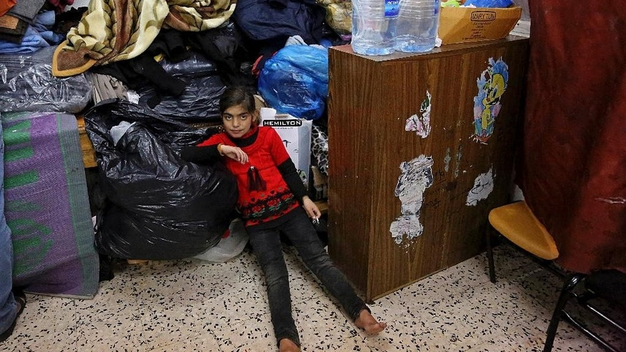 "Sundos Wadiya, 8, sits amid her family's belongings in a classroom at a U.N. school where she and her eleven family members live after their home was destroyed by Israeli strikes during last summer's Israel-Hamas war, in Gaza city, northern Gaza Strip, Tuesday, Jan. 27, 2015. The U.N. Relief and Works Agency said it suspended an aid program for Gaza residents displaced by the war because of a large shortfall in funds from donor countries. Robert Turner, head of the U.N. agency in Gaza, says that ""virtually none"" of the $5.4 billion pledged by the international community in aid to Gaza has reached Gaza and that this is ""distressing and unacceptable."" (AP Photo/Adel Hana)"