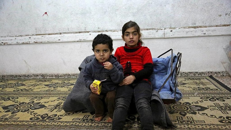 "Sundos Wadiya, 8, and her brother Adnan, 3, sit on a cot  in a classroom at a U.N. school where their eleven family members live after their home was destroyed by Israeli strikes during last summer's Israel-Hamas war, in Gaza city, northern Gaza Strip, Tuesday, Jan. 27, 2015. The U.N. Relief and Works Agency said it suspended an aid program for Gaza residents displaced by the war because of a large shortfall in funds from donor countries. Robert Turner, head of the U.N. agency in Gaza, says that ""virtually none"" of the $5.4 billion pledged by the international community in aid to Gaza has reached Gaza and that this is ""distressing and unacceptable."" (AP Photo/Adel Hana)"