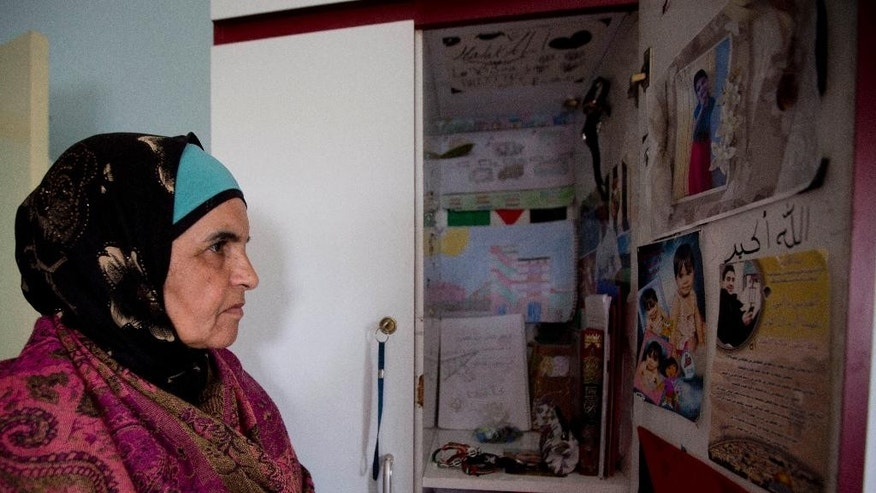In this Tuesday, Jan. 27, 2015 photo, Palestinian Khawla Al-Khatib, looks at posters belonging to her 14-year-old daughter Malak al-Khatib, that is arrested in Israel, in the village of Beitin near the West Bank city of Ramallah. The Palestinian suspect, charged with stone throwing and possession of a knife, entered the courtroom and was sentenced to two months in prison. The scene has played out like many others in Israeli military courts. Except this time, the suspect was a 14-year-old girl. Malak al-Khatib was arrested last month near her sleepy village in the West Bank. Hers is a rare case of a female Palestinian minor held by Israel that has gripped Palestinians, who say her treatment demonstrates Israel's excessive measures against stone-throwing youth. (AP Photo/Majdi Mohammed)