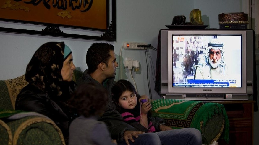 In this Tuesday, Jan. 27, 2015 photo, Palestinian Khawla Al-Khatib, left, sits with her son Yusuf al-Khatib as they watch Ali al-Khatib, father of 14-year-old daughter Malak al-Khatib, detained in Israel, on TV, in the village of Beitin near the West Bank city of Ramallah. The Palestinian suspect, charged with stone throwing and possession of a knife, entered the courtroom and was sentenced to two months in prison. The scene has played out like many others in Israeli military courts. Except this time, the suspect was a 14-year-old girl. Malak al-Khatib was arrested last month near her sleepy village in the West Bank. Hers is a rare case of a female Palestinian minor held by Israel that has gripped Palestinians, who say her treatment demonstrates Israel's excessive measures against stone-throwing youth. (AP Photo/Majdi Mohammed)