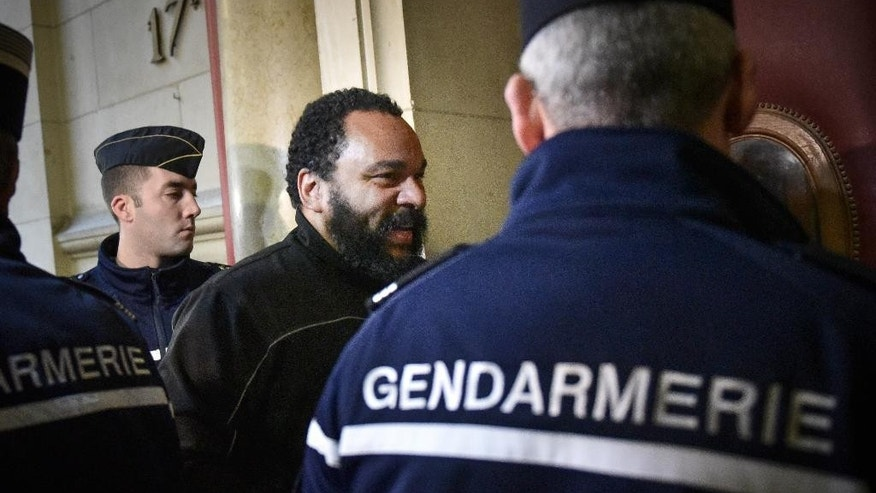 French comic Dieudonne M'Bala M'Bala arrives at the Paris court house, France, to attend his trial,  Wednesday, Jan. 28, 2015. Controversial French comic Dieudonne goes on trial accused of inciting racial hatred by insulting a Jewish journalist with comments about the gas chambers. The trial comes as the French government is cracking down on hate speech and anti-Semitism after deadly terrorist attacks on a kosher market and newspaper Charlie Hebdo. (AP Photo/Zacharie Scheurer)