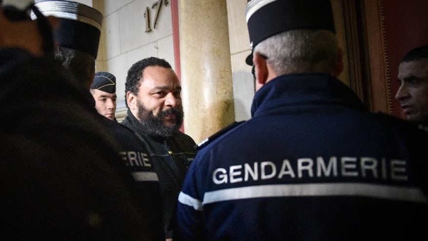 French comedian Dieudonne M'Bala M'Bala arrives at the Paris court house, France, to attend his trial,  Wednesday, Jan. 28, 2015. Controversial French comic Dieudonne goes on trial accused of inciting racial hatred by insulting a Jewish journalist with comments about the gas chambers. The trial comes as the French government is cracking down on hate speech and anti-Semitism after deadly terrorist attacks on a kosher market and newspaper Charlie Hebdo. (AP Photo/Zacharie Scheurer)