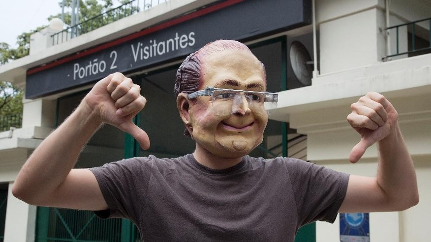 A demonstrator wearing a mask depicting Sao Paulo's Governor Geraldo Alckmin protests against the rationing of water outside the official residence of the Governor in Sao Paulo, Brazil, Monday, Jan. 26, 2015. The system of reservoirs and rivers that provide water to millions in this city have received less rainfall than hoped in the worst drought in more than 80 years, raising fears they won't be replenished as hoped. (AP Photo/Andre Penner)
