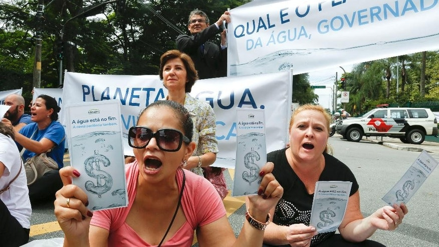 "Demonstrators hold signs that reads in Portuguese ""The water is at its end, our patience too,"" as they protest against the rationing of water outside the official residence of Sao Paulo's Governor Geraldo Alckmin in Sao Paulo, Brazil, Monday, Jan. 26, 2015. The system of reservoirs and rivers that provide water to millions in this city have received less rainfall than hoped in the worst drought in more than 80 years, raising fears they won't be replenished as hoped. (AP Photo/Andre Penner)"