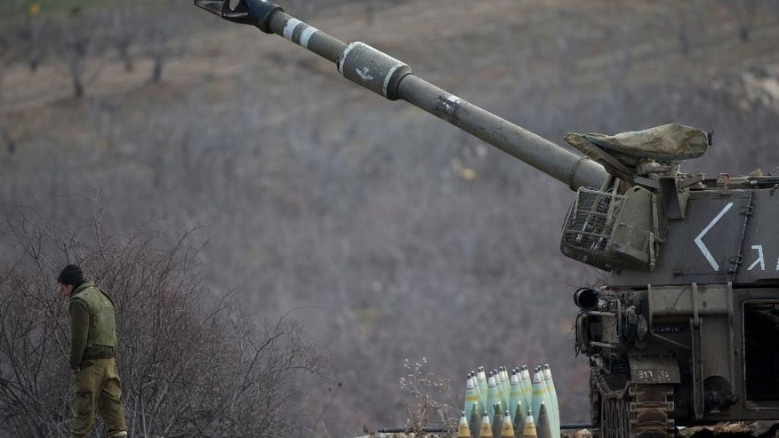 An Israeli soldier stands next to a mobile artillery unit in the Israeli-controlled Golan Heights near the border with Syria, Wednesday, Jan. 28, 2015. The Israeli military says it has struck Syrian army artillery posts in response to rockets that landed the previous day in the Israeli-held Golan Heights.(AP Photo/Ariel Schalit)