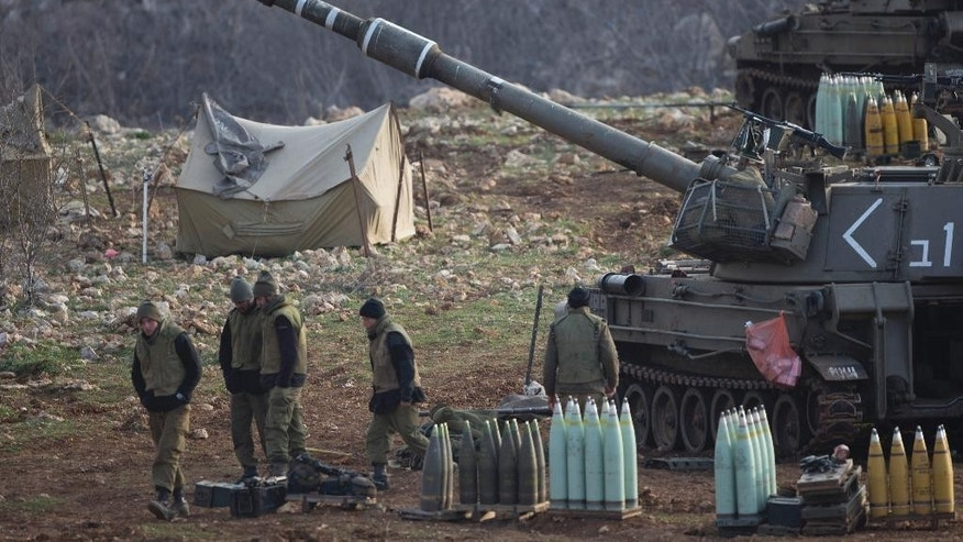 Israeli soldiers stand next to a mobile artillery unit in the Israeli-controlled Golan Heights near the border with Syria, Wednesday, Jan. 28, 2015. The Israeli military says it has struck Syrian army artillery posts in response to rockets that landed the previous day in the Israeli-held Golan Heights.(AP Photo/Ariel Schalit)