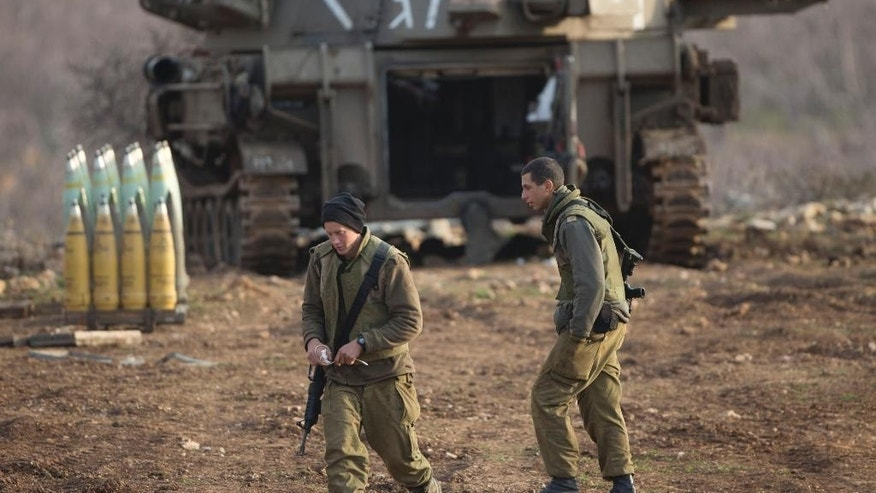 Israeli soldiers walk next to a mobile artillery unit in the Israeli-controlled Golan Heights near the border with Syria, Wednesday, Jan. 28, 2015. The Israeli military says it has struck Syrian army artillery posts in response to rockets that landed the previous day in the Israeli-held Golan Heights. (AP Photo/Ariel Schalit)
