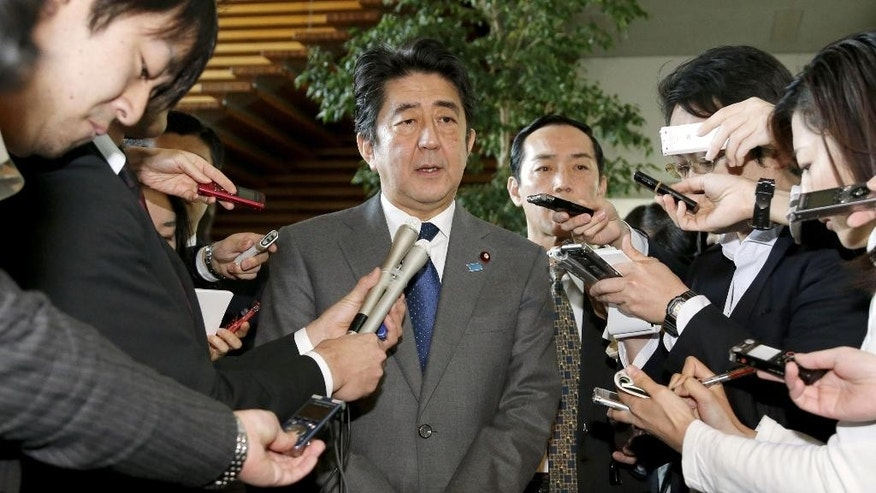 Japan's Prime Minister Shinzo Abe speaks to reporters after a meeting on the hostage crisis, at his official residence in Tokyo Wednesday, Jan. 28, 2015. Japanese officials were tightlipped Wednesday as secret talks in Jordan sought to secure the freedom of a Japanese journalist and a Jordanian pilot captured by Islamic State extremists and purportedly threatened with death within 24 hours. (AP Photo/Kyodo News) JAPAN OUT, MANDATORY CREDIT