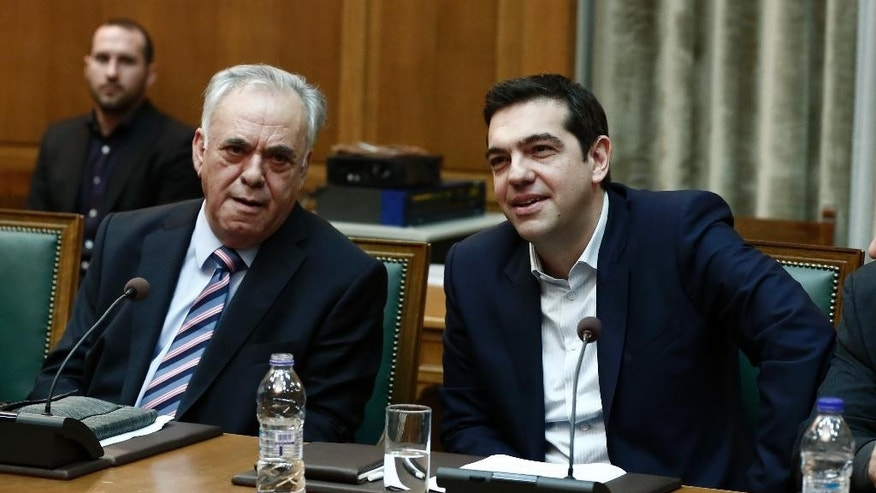 Greece's Prime Minister Alexis Tsipras, right, and Deputy Prime Minister Giannis Dragasakis attend the first cabinet meeting of the new government at the Parliament in Athens, on Wednesday, Jan. 28, 2015. Greece's new left-wing government was sworn in Tuesday after a landmark general election victory at the weekend. (AP Photo/Petros Giannakouris)