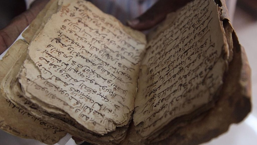 A  man holds an ancient manuscripts that will need to be restored after being damaged in Bamako, Mali, Tuesday, Jan. 27, 2015. After being saved from destruction at the hands of Islamic extremists, thousands of ancient manuscripts from the fabled northern Mali city of Timbuktu now face a less dramatic but still worrying threat: weather and poor storage conditions in their new location that scholars say could lead to permanent damage. (AP Photo/Baba Ahmed)