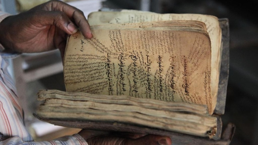 A man holds an ancient manuscript that will need to be restored after being damaged in Bamako, Mali, Tuesday, Jan. 27, 2015. After being saved from destruction at the hands of Islamic extremists, thousands of ancient manuscripts from the fabled northern Mali city of Timbuktu now face a less dramatic but still worrying threat: weather and poor storage conditions in their new location that scholars say could lead to permanent damage. (AP Photo/Baba Ahmed)
