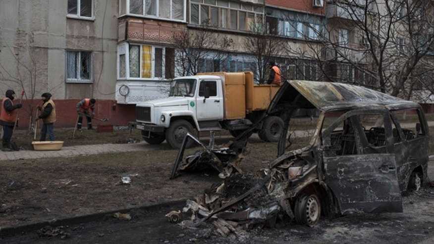 Jan. 27, 2015: Municipal workers clear away debris at the site of Saturday's shelling in Mariupol, Ukraine. (AP)