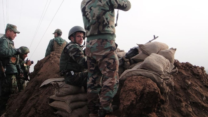 In this Tuesday, Jan. 27, 2015 photo, Kurdish Peshmerga fighters man a front line position in Ninevah province, northern Iraq. The Iraqi Kurdish fighters retaking territory from Islamic State militants have found surprising ambivalence in areas they free from the jihadis' oppressive rule. Locals have swiftly shaken off the imposed Islamic lifestyle _ but as Sunnis, from the same ethnic group as the militants, many are bracing for treatment as collaborators nonetheless. An AP team traveling with the Kurds found the road to Mosul, a coveted prize in the battle for Iraq, strewn with suspicion and fear. (AP Photo/Vivian Salama)