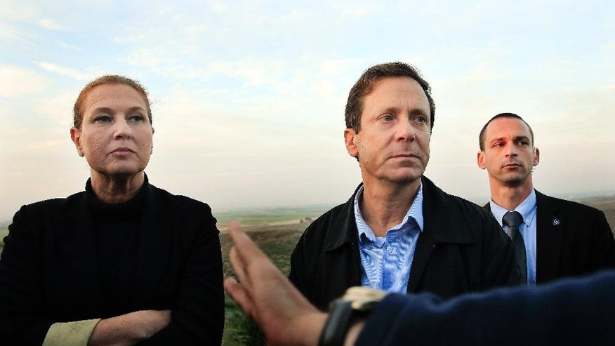 FILE - In this Thursday, Dec. 11, 2014 file photo, Israeli politicians Isaac Herzog, right, and Tzipi Livni listen during a tour along the Israel and Gaza Strip border. When Prime Minister Benjamin Netanyahu dissolved his unwieldy coalition and called new elections last month, he appeared to be a lock to return to office. But a new center-left alliance has suddenly surged in the polls past his ruling Likud party to become the largest parliamentary faction and turned the March 17 vote into a toss-up. (AP Photo/Tsafrir Abayov, File )