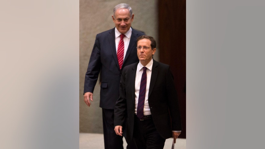 FILE  - In this Monday, Jan. 20, 2014 file photo, Israel's opposition leader and Labor Party leader Isaac Herzog, front, walks past Israeli Prime Minister Benjamin Netanyahu at the Knesset, Israel's Parliament, in Jerusalem. When Prime Minister Benjamin Netanyahu dissolved his unwieldy coalition and called new elections last month, he appeared to be a lock to return to office. But a new center-left alliance has suddenly surged in the polls past his ruling Likud party to become the largest parliamentary faction and turned the March 17 vote into a toss-up. (AP Photo/Ariel Schalit, File)