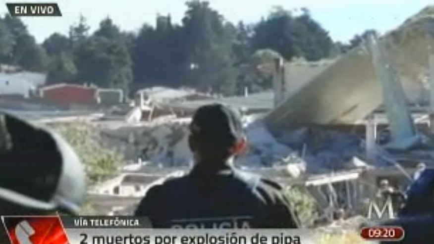 In this video frame grab image taken from Milenio TV via APTN, police look at the scene where a gas tank truck exploded outside a maternity and children's hospital in Mexico City, Thursday, Jan. 29, 2015. At least two persons reported dead and dozens injured. (AP Photo/Milenio TV via APTN)