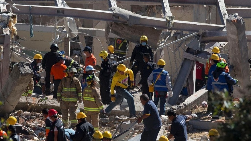 Rescue workers comb through the rubble of a children's hospital after a gas truck exploded, in Cuajimalpa on the outskirts of Mexico City, Thursday, Jan. 29, 2015. The powerful explosion shattered the hospital on the western edge of Mexico's capital, killing at least three adults and one baby and injuring dozens. (AP Photo/Rebecca Blackwell)