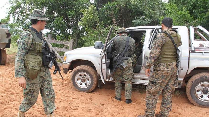 "Paraguayan army soldiers inspect a vehicle belonging German citizens Robert Natto and Érika Reiser, who were killed by the ""Paraguayan People's Army"", (EPP) after they where kidnapped on Wednesday night at Yby Yau, in Northern Paraguay, Thursday, Jan. 29, 2015. Natto and Reiser had a cattle ranch in northern Paraguay near Paraguay's People Army operations zone. (AP Photo/Enrique Zarza)"