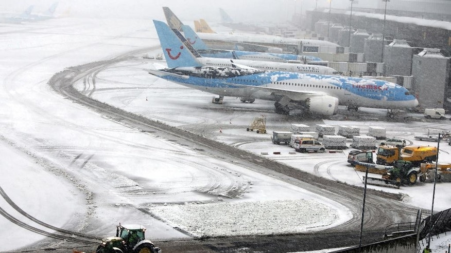 Tractors clear the snow from the runways at Manchester Airport's Terminal 1, Thursday Jan. 29, 2015, in Manchester, England. Ice and snow have caused travel disruptions in England and Scotland, forcing the closure of Manchester Airport and cancelling dozens of train services. (AP Photo/PA, Peter Byrne) UNITED KINGDOM OUT